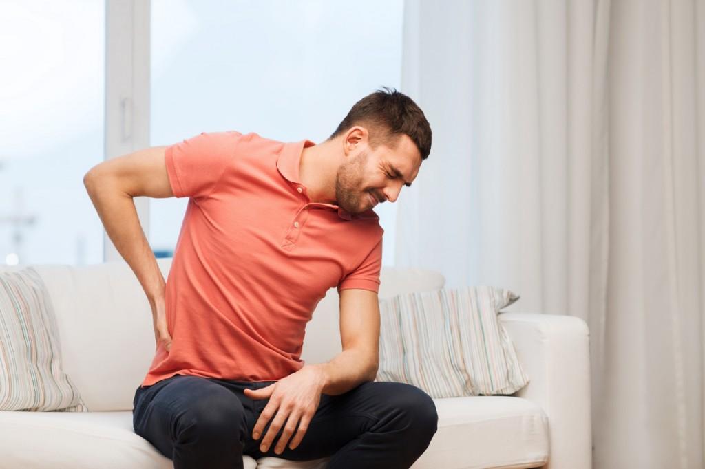 man on sofa holding back
