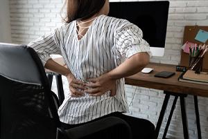 woman back pain desk
